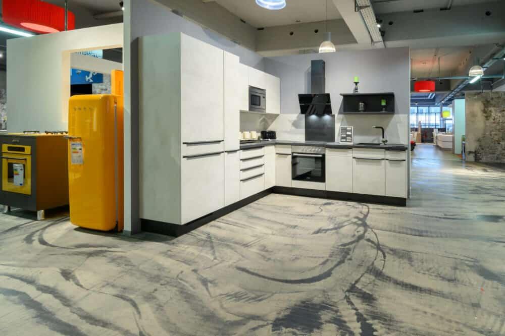 Moderne L-Küche Beton Küchenfronten Griffleisten und E-Geräte
