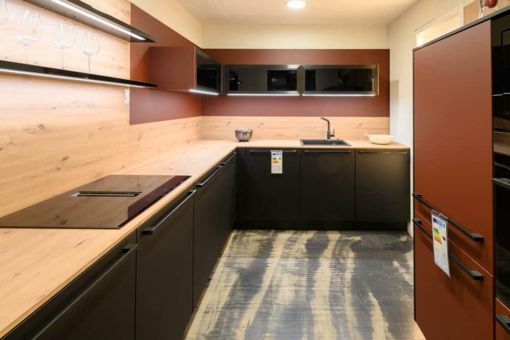 Moderne L-Küche schwarz matt lack mit Holz Arbeitsplatte und rotem Wandschrank