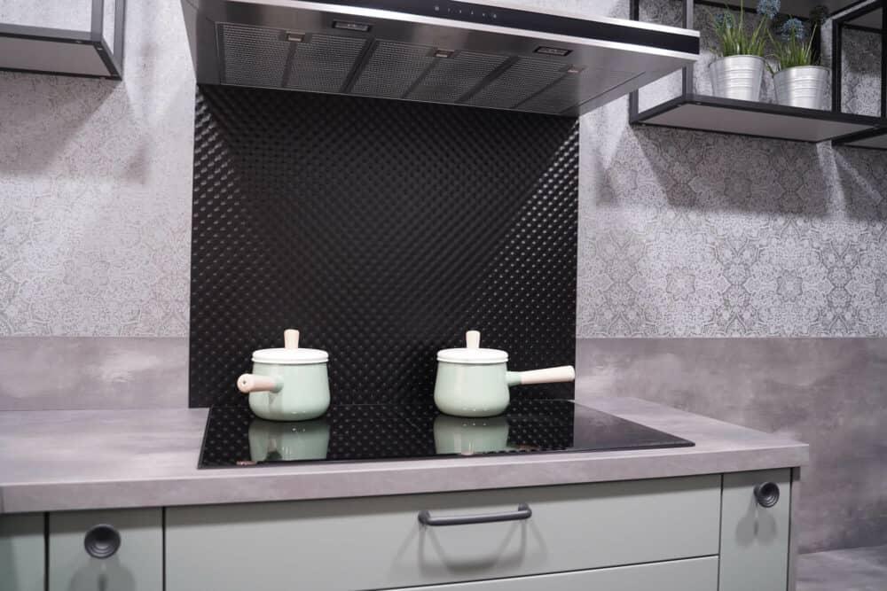 Landhaus Küche grün mit grauer Arbeitsplatte und Kochfeld